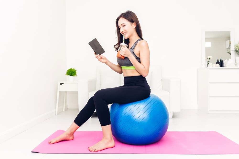 Sport woman in sportswear sitting relax reading a book and drink